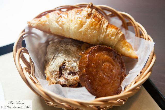Basket filled with olive roll, kouig amann, and croissant