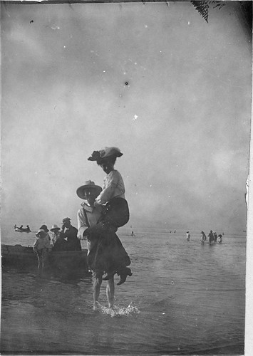 A man carrying a woman ashore from a rowing boat, 1914 | by State Library of South Australia