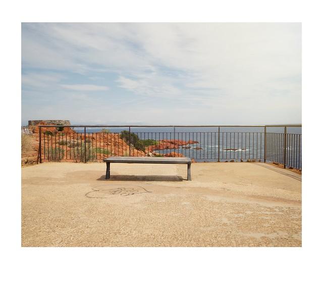 Graffiti, bench, railings and view.