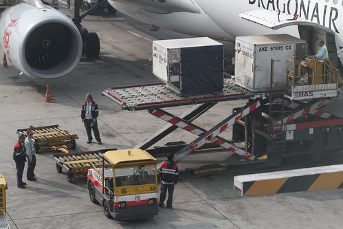 Loading ULD cargo containers beneath a Dragonair jet