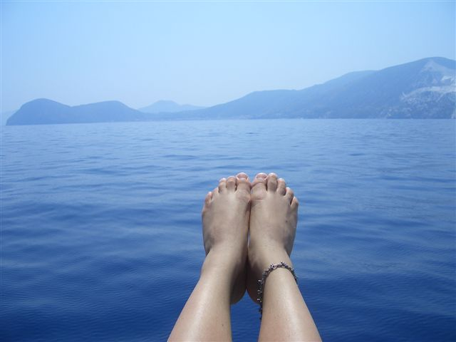 Relaxing at the front of the sail boat, Eolie, Italy