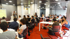 En la imagen se puede ver a los/as Yuzzers sentados en distintas mesas de trabajo escuchando las ideas de negocio de sus compañeros/as