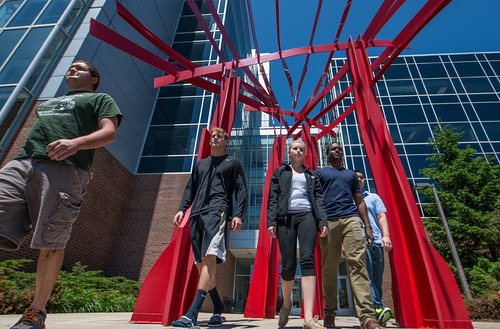 "Students walk through Russell Thayer's sculpture, ""Windrapids II"" on near the south entrance to the Biomedical and Physical Sciences building. Explore more sculptures on campus at MSU Campus Sculpture Tour. (Photo/D.L. Turner)"