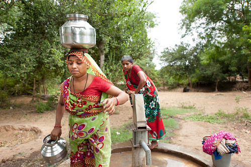 two women getting water from a pump