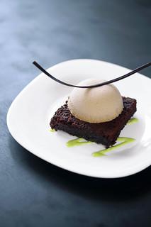 Plated dessert: dark chocolate brownie with praline mousse and pistachio cream