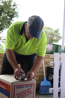 Image of a removalist taping a box for removal | by sunset_removals