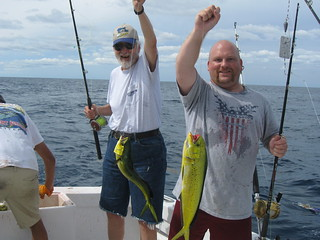 Photo of two men holding up two mahi-mahi