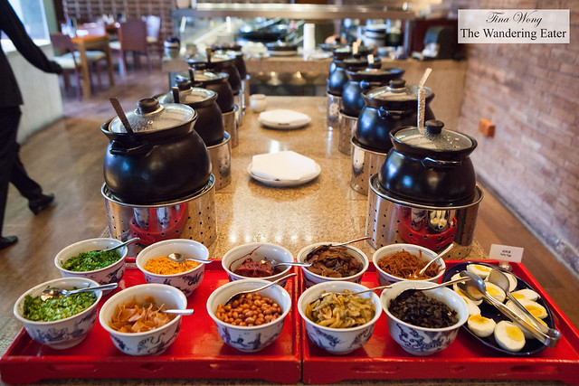 Small pots of various congees, soups and soybean milk and a topping bar at Made in China's breakfast buffet