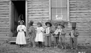 "Seven children holding letters that spell ""goodbye"" at Fort Simpson Indian Residential School, Northwest Territories / Sept enfants tenant des lettres formant le mot « goodbye » au pensionnat indien de Fort Simpson (Territoires du Nord-Ouest)"