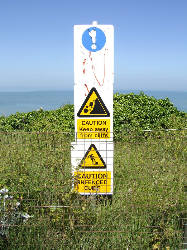 Unfenced cliff warning. Behind a fence.