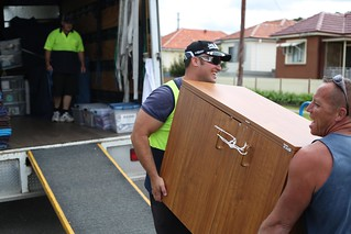Image of man and van lifting furniture onto the removal truck for transport. | by sunset_removals