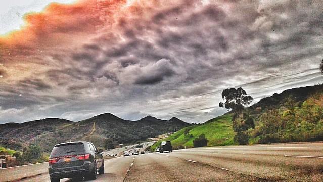 Intimidating Sky! #losangeles #cali #tree #aftertherain #nomoredrought #traffic #dramaticsky #california #beautifulsky #green #mountains #downhill #speed #motion