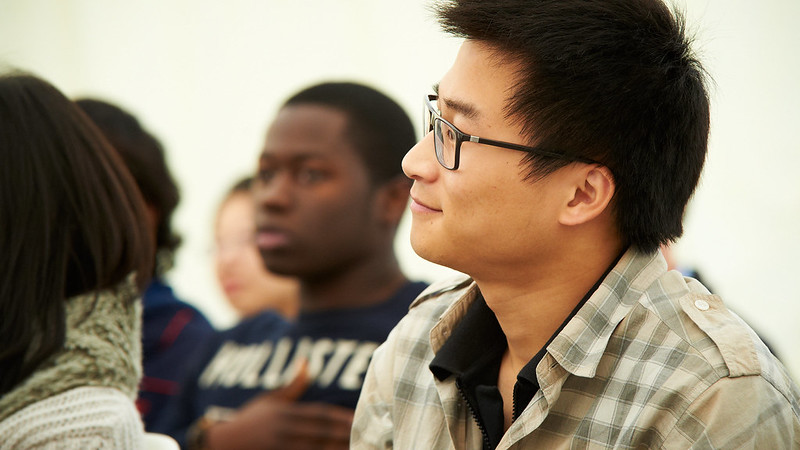 A male East-Asian student sat down in a lecture in the foreground with a black male student in the background