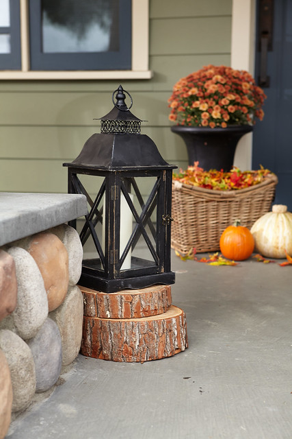 Lantern on a doorstep with flower pot and fall squash in the background
