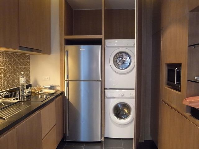 <p>左はキッチン、正面に冷蔵庫と洗濯機と乾燥機、右側には電子レンジや食器などがあります。</p>