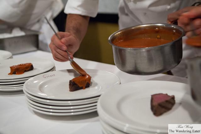 Chef saucing the steak dish
