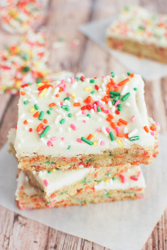 Cake Batter Blondie Bars - chewy blondies filled with rainbow sprinkles, topped with buttercream frosting, and sprinkled with more sprinkles!