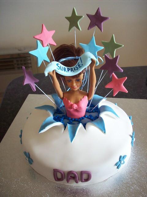 Girl bursting out of cake