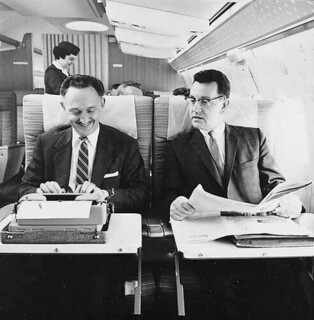 Two men on Northwest Airlines aircraft, one using typewriter, with female flight attendant in background | by UW Digital Collections