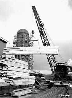 Crane lifting cut planks of lumber for loading onto flat barges / Une grue soulève des planches pour les charger sur des barges planes