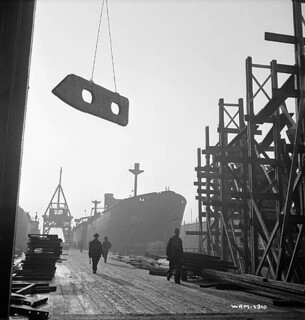 Dockyard scene as frame for keel is hoisted away from the wharf / Scène de chantier maritime où une ossature de quille est hissée à partir du quai