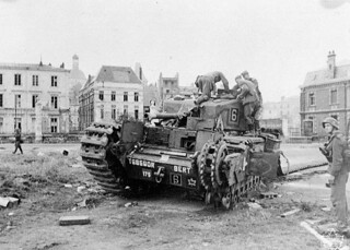 "German troops examining ""Churchill"" tank of the Calgary Regiment abandoned during the raid on Dieppe / Des soldats allemands examinant un char d'assaut « Churchill » du Régiment de Calgary abandonné durant le raid sur Dieppe"