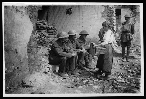 Little French girl braves the shells to sell her wares to our Tommies not far behind the line