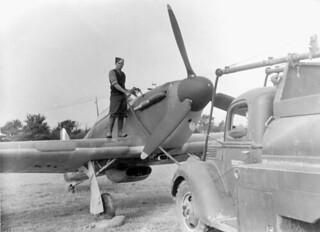 An unidentified airman refuelling a Hawker Hurricane I aircraft of No. 1 (F) Squadron, RCAF [graphic material]. / Un aviateur non identifié réapprovisionne en combustible un aéronef Hawker Hurricane I du 1er Escadron (F), ARC.