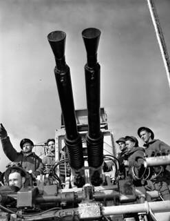 A Bofors 40 mm anti-aircraft gun crew on the destroyer HMCS Algonquin at action stations in Arctic waters. / L'équipe de mise en uvre du canon antiaérien Bofors de 40 mm à bord du destroyer NCSM Algonquin à des postes de combat dans les eaux arctique