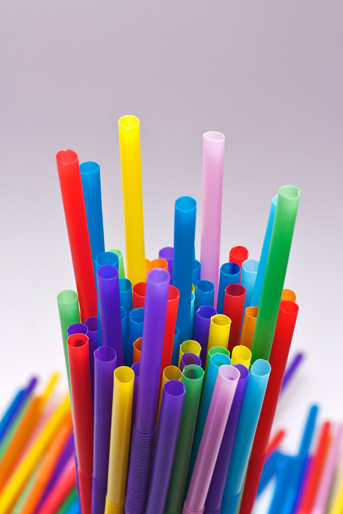 A bunch of colorful plastic straws in a glass