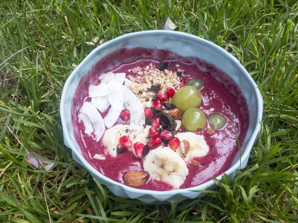 Bowl mit Kokos-Chips, Bananen, Mandeln, Granola, Granatapfelkernen und selbst gehobelter dunkler Schokolade