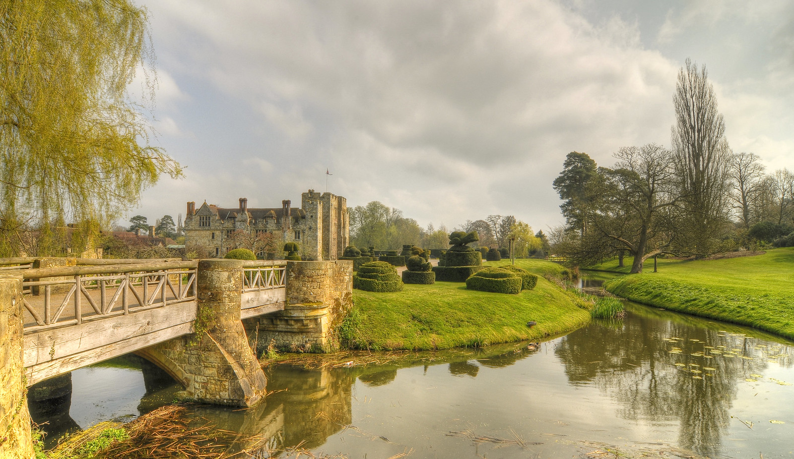 Hever Castle across lake v2 See v1 for comparison. This is my second shot of Hever Castle from across the 'lake' at the front. It has a better angle on the bridge and I like the way the lake takes up more of the foreground, but it is less panoramic. I think I prefer this one, but I'm not sure!