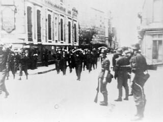 Canadian prisoners of war being lead through Dieppe by German soldiers. / Les soldats allemands mènent les prisonniers de guerre canadiens à travers Dieppe