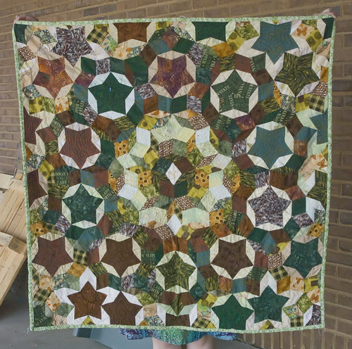 It's proving to be a difficult quilt to photograph. I originally shot a photo of it in our department, and the colors looked muddied, so we waited for the thunderstorm to end and reshot it outside on the back loading dock. It's not great, but better.  Finished size is about 41 inches per side.