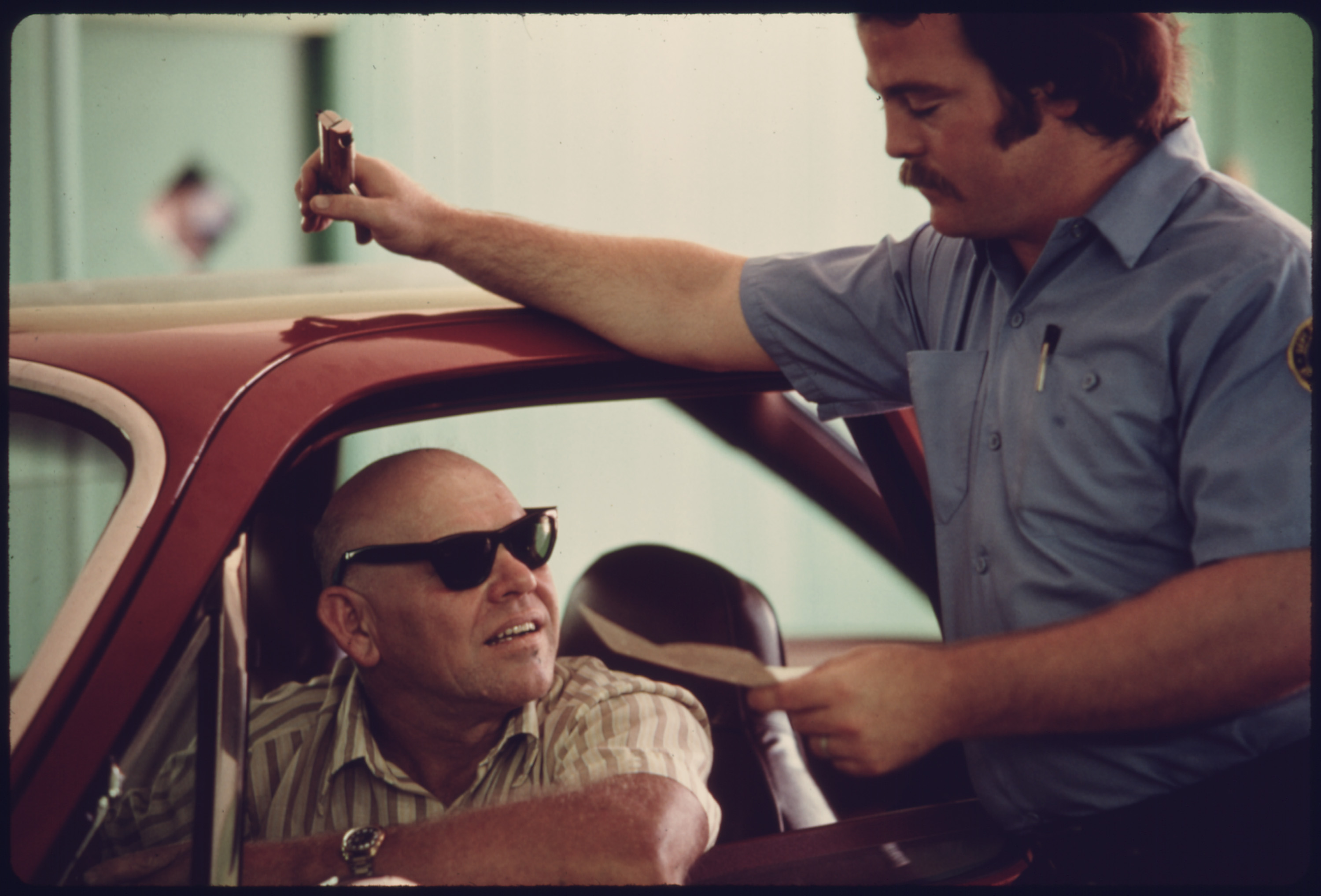 Motorist and Public Works Department Employee Discuss the Results of the Car's Performance after Testing at an Auto Emission Inspection Station in Norwood, Ohio...08/1975