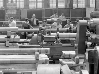 Workmen operate lathes to cut the barrel of 25-pounder field guns / Des ouvriers travaillant sur des tours coupent les tubes de canons de campagne de 25 livres