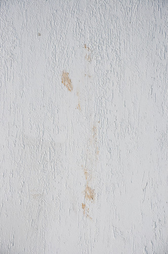 Texture of a white wall with a brown stain