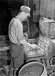 Workman placing hand grenades into a hand grenade mould at the Frost and Wood plant. / Des ouvriers plaçant des grenades à main dans un moule à grenades à main à l'usine Frost and Wood