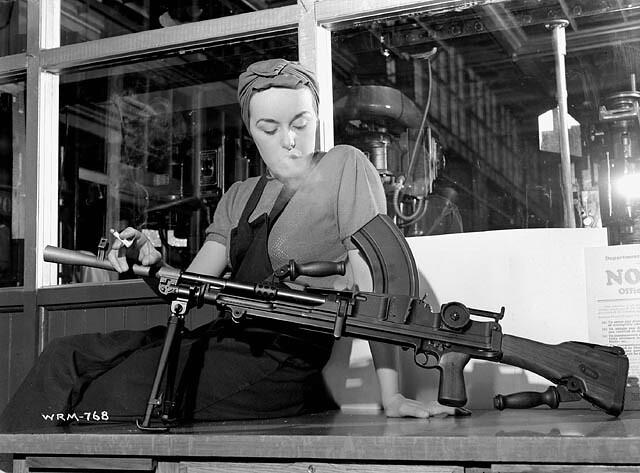 "Veronica Foster, known as ""The Bren Gun Girl,"" poses with a finished Bren gun at the John Inglis & Co. plant / Veronica Foster, surnommée « la fille au fusil-mitrailleur » pose avec un fusil-mitrailleur Bren assemblé à l'usine John Inglis & Co."