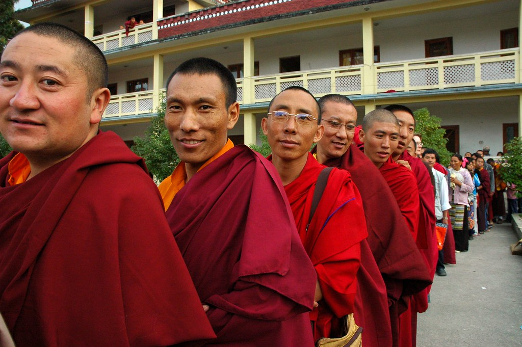 Pleased and happy Tibetan monks, in a line waiting for lon