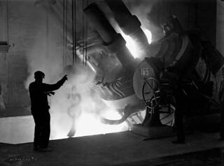 Workman stands beside a furnace at the Stelco Steel Co., directing the pouring of molten steel into a ladle. / Un ouvrier se tient à côté d'un four et oriente le coulage d'acier fondu dans une poche de coulée à la société Stelco Steel Co