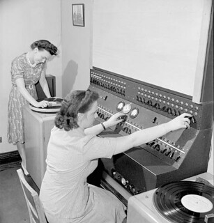 Women workers select piped music to play in the central control room of a Montreal factory / Des ouvrières choisissent des airs de musique pour les diffuser dans la salle de commande centrale d'une fabrique de Montréal