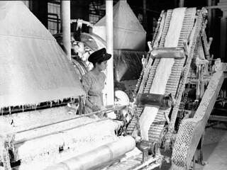 The operator, Clémence Gagnon, watches a machine carding asbestos fibre, Johns Manville factory, Asbestos, Que., 1944 / L'opératrice, Clémence Gagnon, observe la machine à carder les fibres d'amiante, usine Johns Manville, Asbestos, Qc, 1944