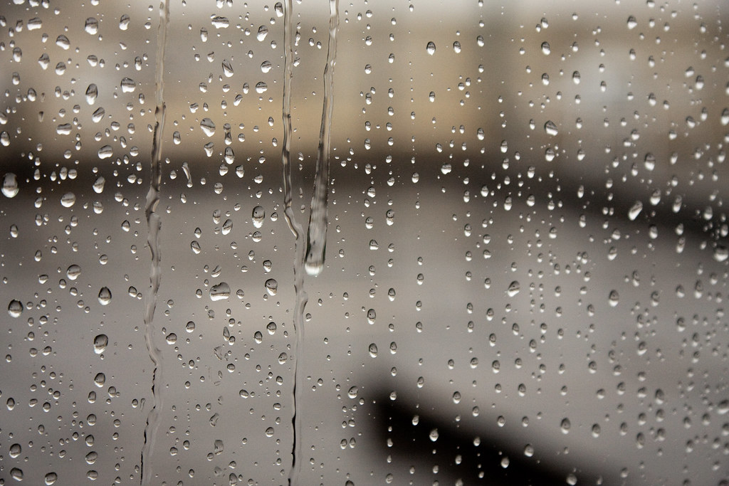 Raindrops falling down a window pane