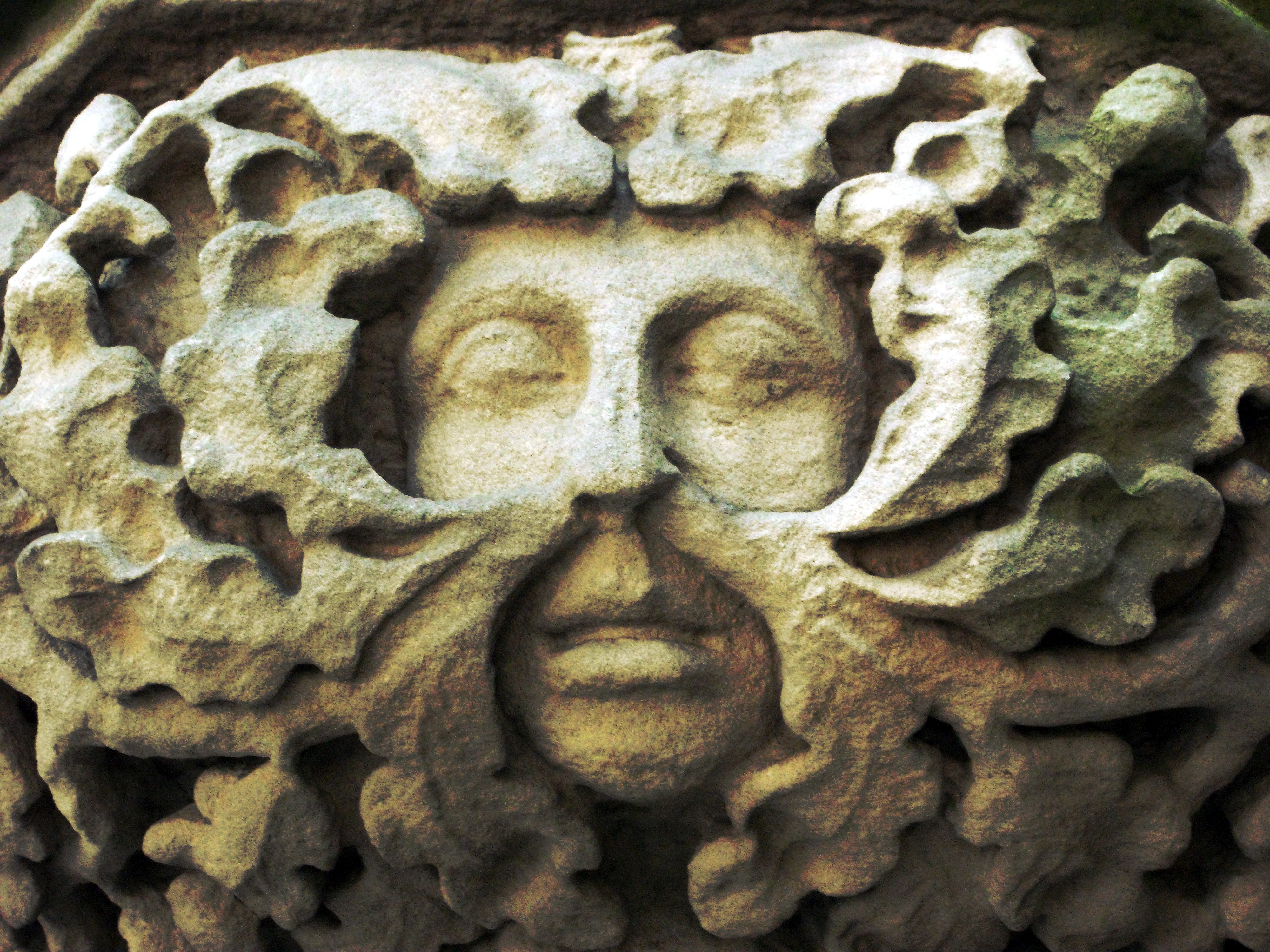 Stone carving of a Green Man with foliage extruding from his nose