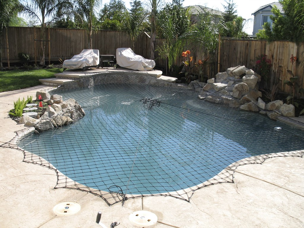 A Katchakid pool safety net cover in black. | Meticulously d ...