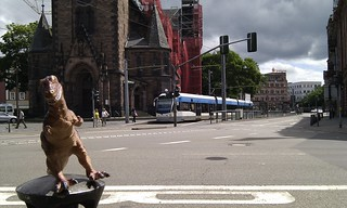 20100612_-_Mobile_City_Walk_Saarbruecken_093_-_Dino_vor_Johanneskirche_2_mit_Saarbahn