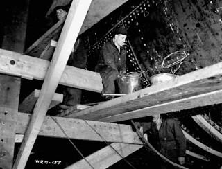 Workmen rivet plates on ribs of corvettes. / Des ouvriers rivent les plaques sur les membrures de corvettes