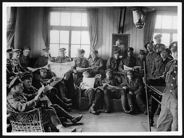 Convalescent soldiers in France in the corner of a reading-room at a recreation hut provided for them by the B.R.C.S.
