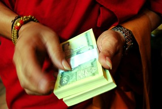 Tibetan Buddhist monk in red robes handing out money in 100 ruppee notes, the donations, to individual lamas, monks and nuns, Tharlam Monastery, Kathmandu, Nepal | by Wonderlane